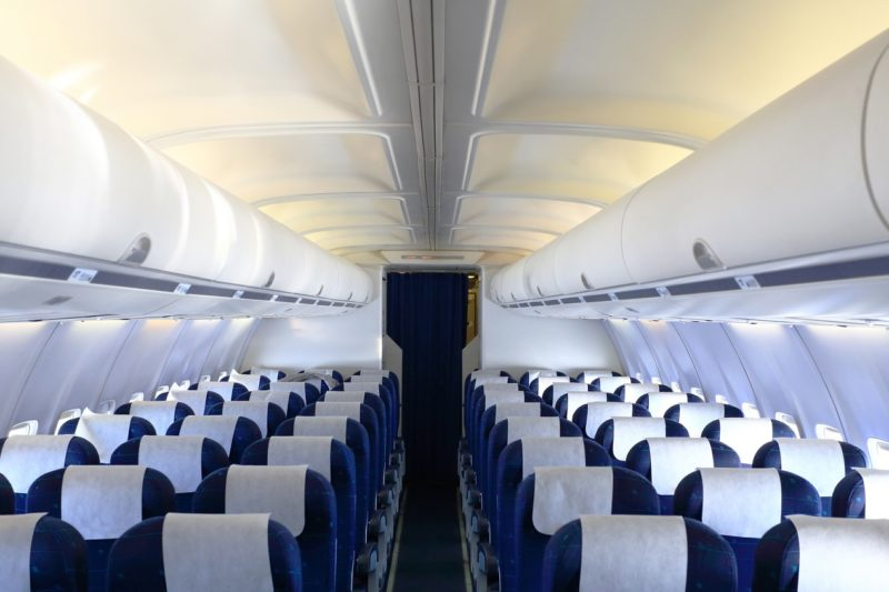 Empty cabin of airplane with blue seats and white panel