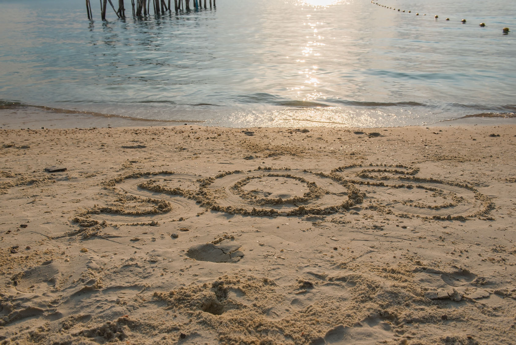 Word  SOS  Write in sand on the beach  .